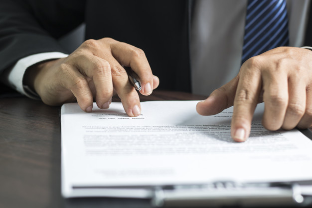 businessman or lawyer reading and signing on contract paper on t